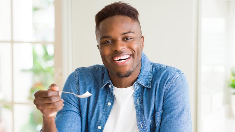 man holding spoon with yogurt