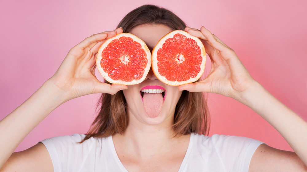 woman holding sliced grapefruit over eyes