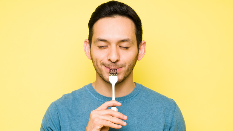 man with fork in mouth