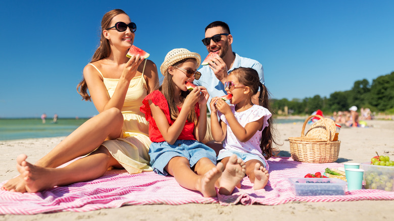 A family eating watermelon slices at the beach