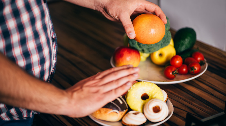 Tight shot of a person choosing an orange from a bowl while holding out a hand saying no to donuts