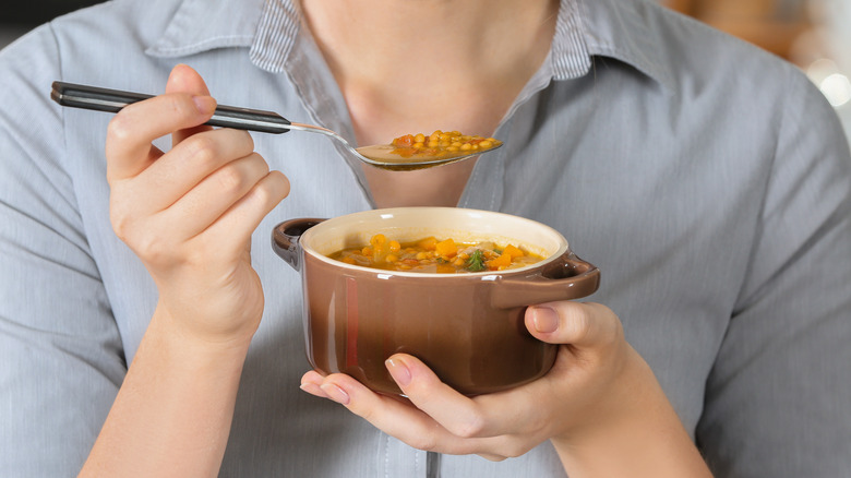 woman eating lentil soup
