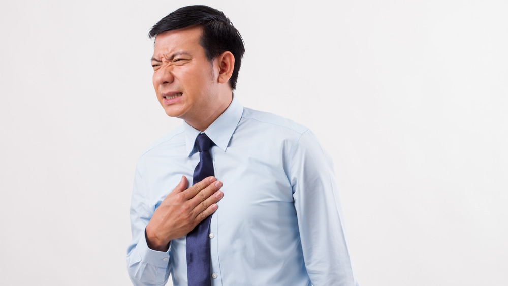 A distressed man rubbing his chest due to heartburn