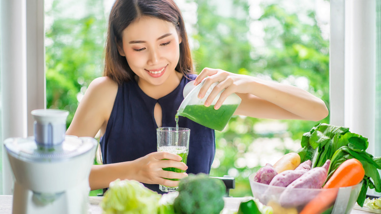 Young woman pouring green juice