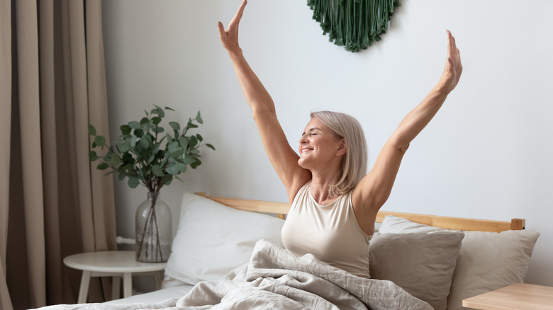 Woman stretching in bed waking up happy with energy