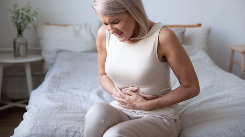 Woman sitting on bed clutching her stomach in pain