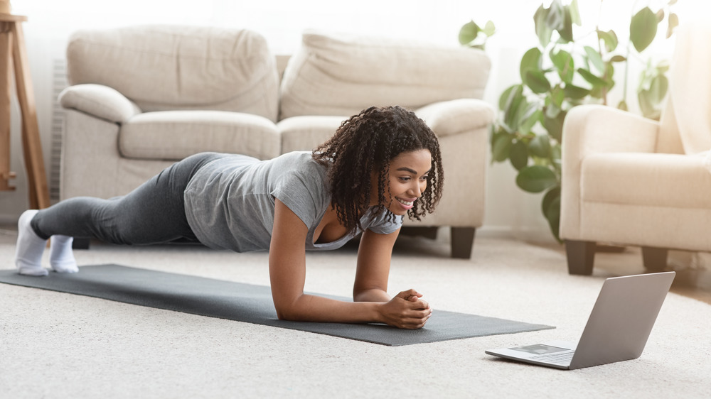 Fit black woman doing yoga plank while watching online tutorial on laptop