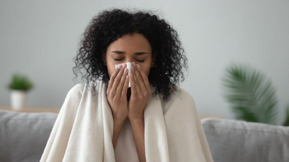 sick woman using a tissue