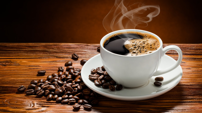 Steaming cup of decaf coffee with coffee beans