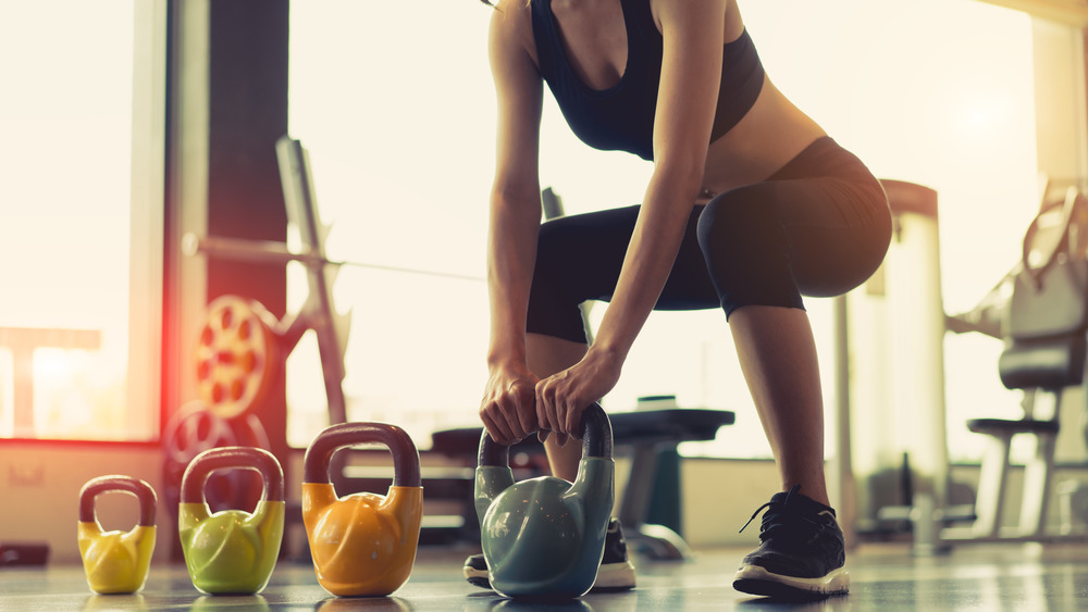 cropped photo of woman with kettlebells