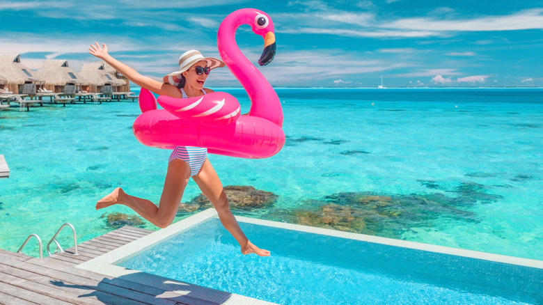young woman jumping in a swiming pool with a pink flamenco floatie