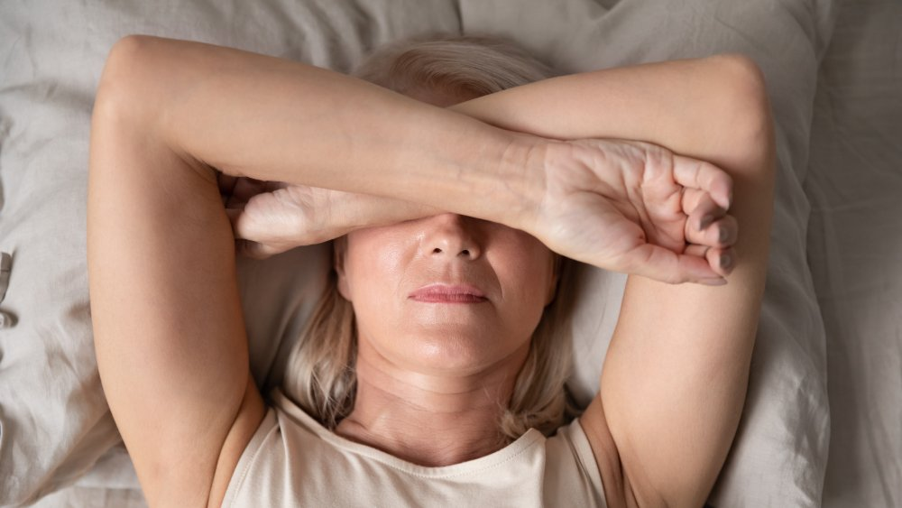 Sleepless woman close up, lying in bed, covering eyes with hands feeling headache or migraine