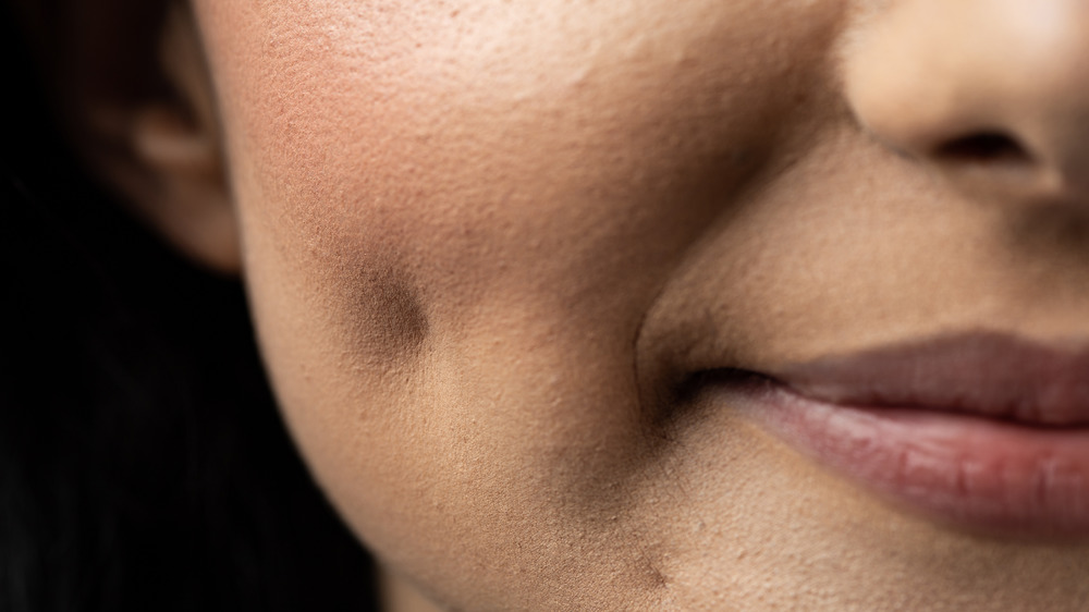 Close up of woman's face with cheek dimple