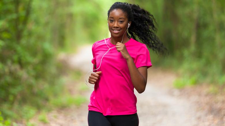 Woman jogging outside with earphones in