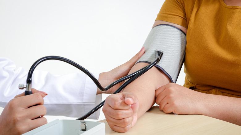 woman using blood pressure cuff