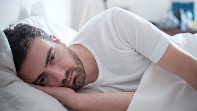 A depressed man laying in bed