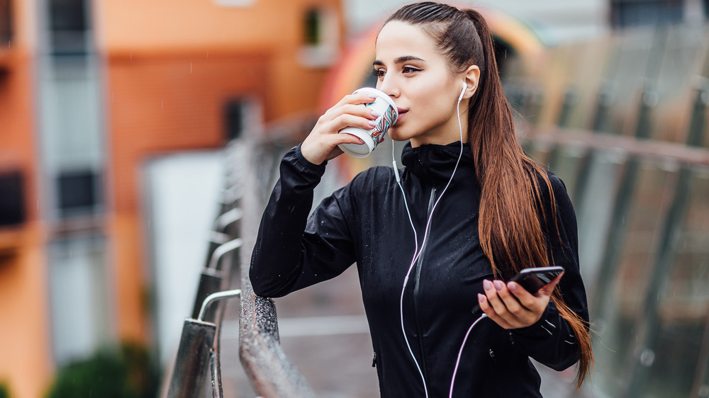 Woman drinking coffee while running