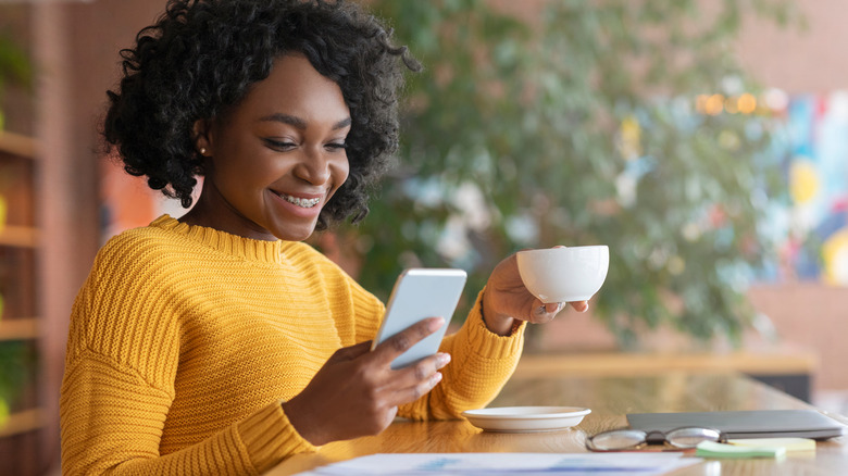 Woman holding coffee cup and phone
