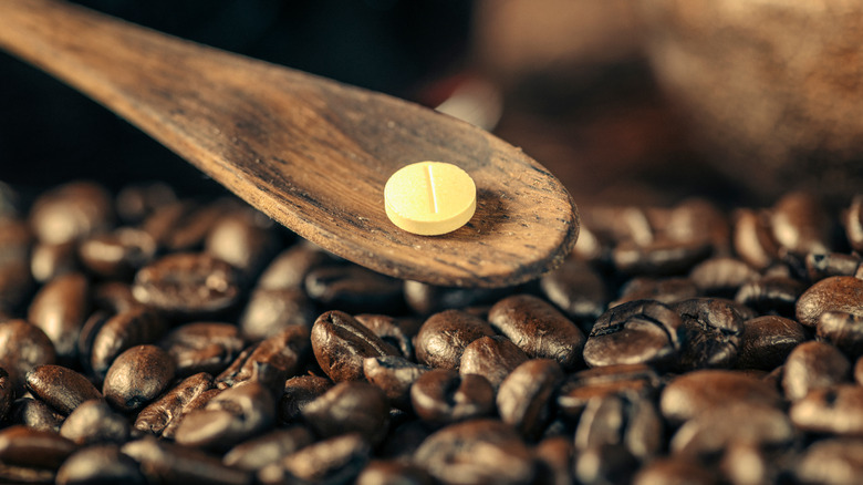 pill on a wooden spoon above coffee beans