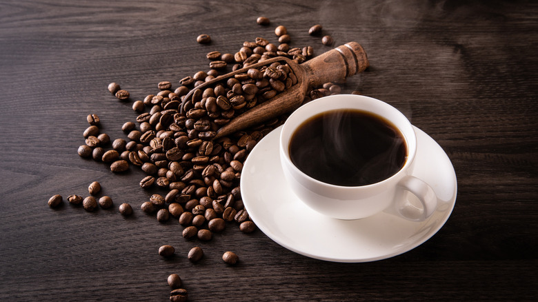 Cup of black coffee with coffee beans on the table
