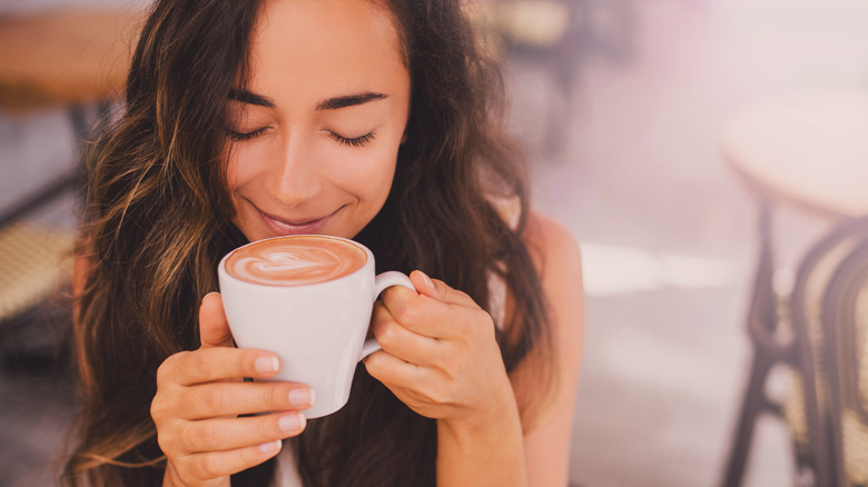 Women smelling cup of coffee