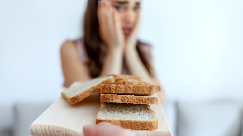 woman staring cautiously at slices of bread