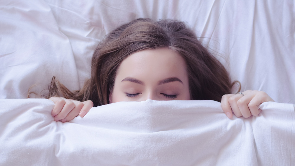 woman sleeping under the bed covers