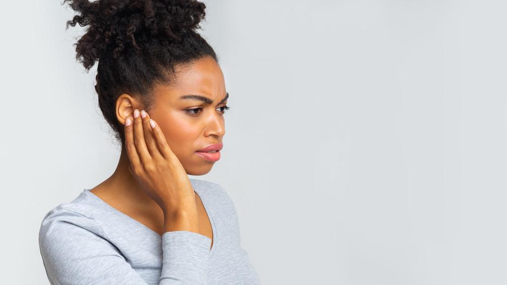 Black woman touching her ear in pain