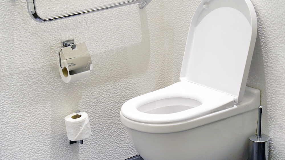 White toilet with white wall in background