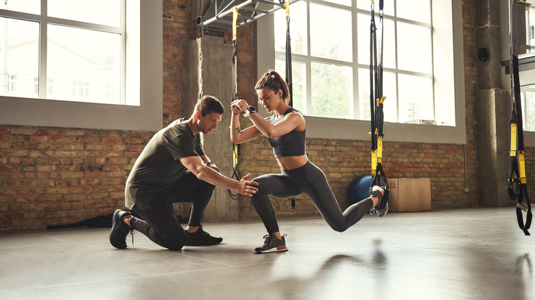 A woman works out with a personal trainer
