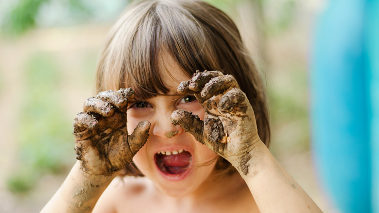 Young boy smiling with muddy hands