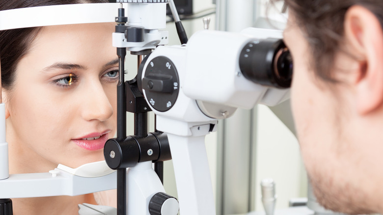 Eye doctor checking patient's eyes with a binocular slit-lamp