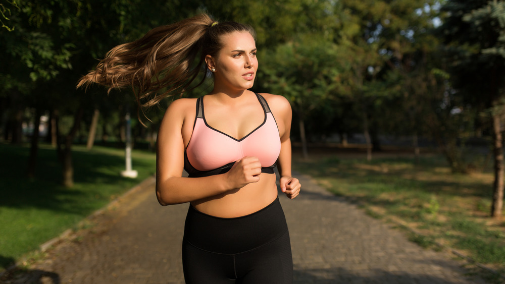 Young woman in sporty top and leggings jogging