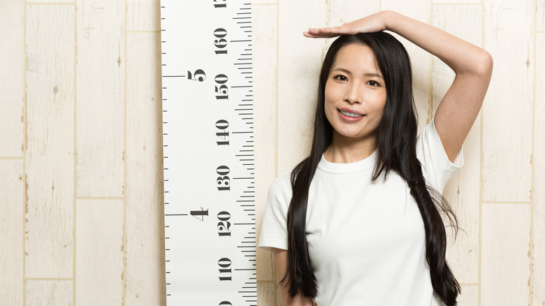 woman checking her height against a ruler