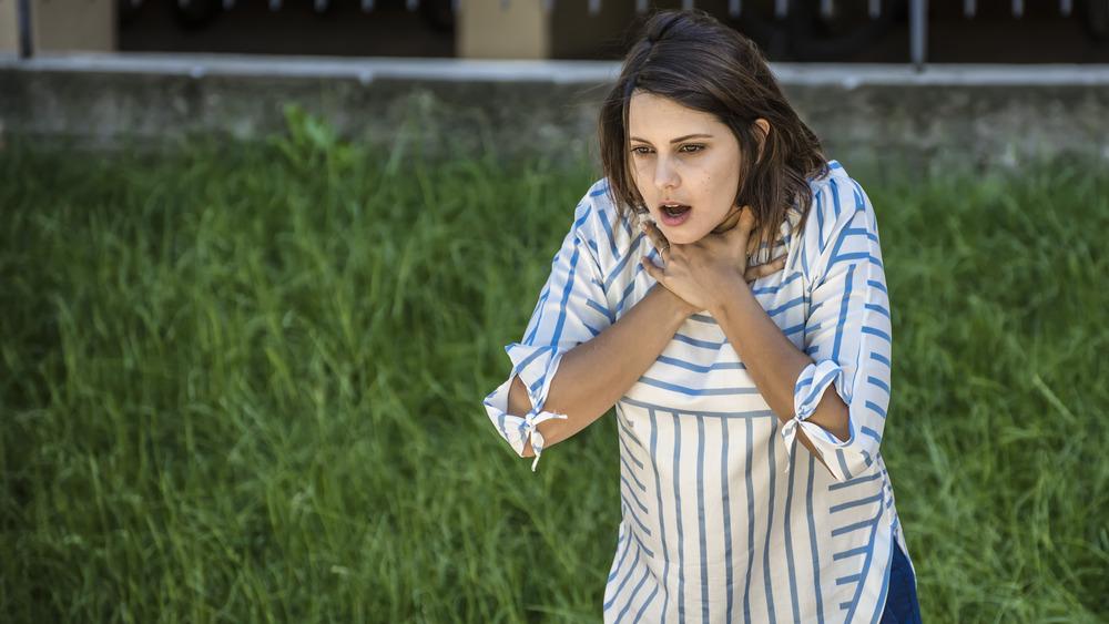 Woman with hands around throat choking