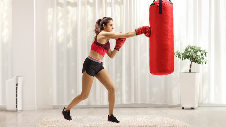 A woman hitting a punching bag in a home gym