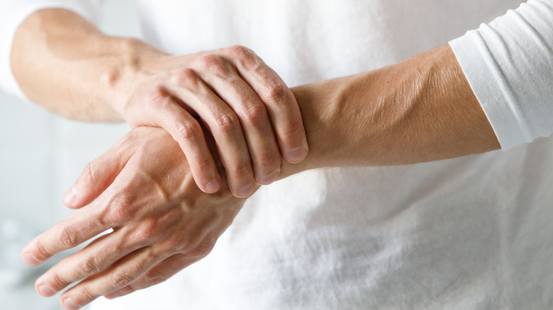 Person in white shirt holding hand and wrist
