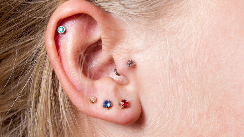 Close up of ear with multiple piercings