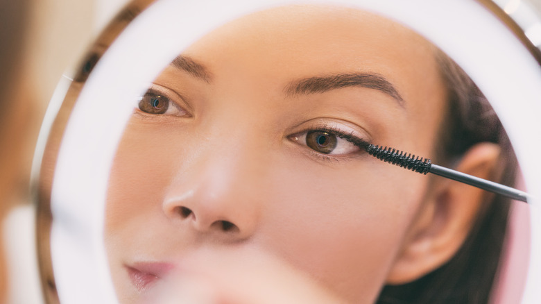 White woman applying mascara in front of a mirror