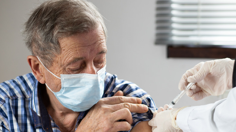 elderly man getting COVID-19 vaccination