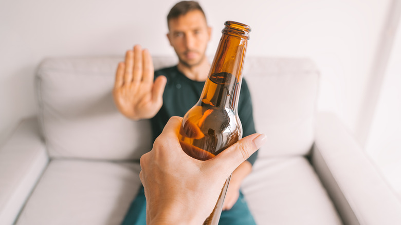 a man gesturing no to an offered bottle of beer