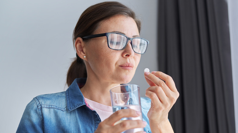 Woman with glasses taking a pill with a glass of water