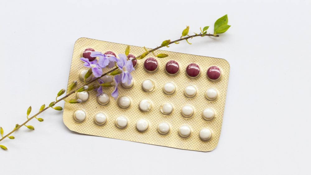 Pack of birth control pills with purple flower