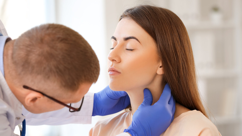 Doctor palpating thyroid of young woman
