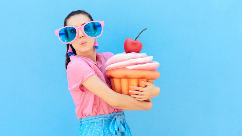 woman clutching giant cupcake