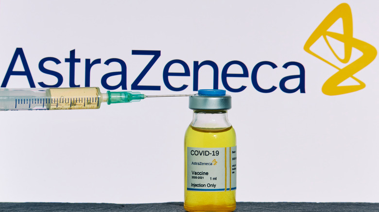 The AstraZeneca logo behind a bottle of vaccine and a syringe
