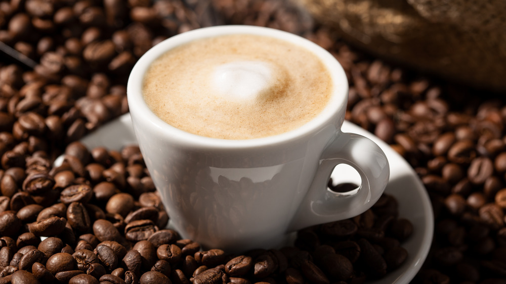 A milky coffee drink sitting on coffee beans