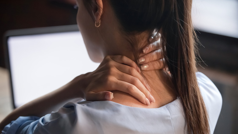 Woman grasping neck