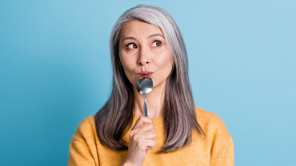 woman with empty spoon to mouth