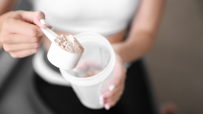 A woman holds a scoop of protein powder